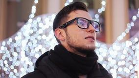 L'homme barbu élégant à célèbrent de Noël, lumières et l'arbre de nouvelle année de ville s'est reflété dans les verres clips vidéos