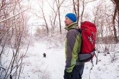 L'homme barbu avec le petit chien marche dans la forêt d'hiver Photos libres de droits