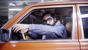 L'homme barbu bel avec de longs cheveux ouvre la fenêtre de voiture rouge et commence à parler clips vidéos