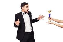 L'homme barbu bel dans un costume noir est remis la tasse de champion Le type est très sincèrement heureux au sujet du gain photo stock