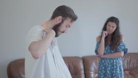 L'homme barbu bel demandant son conseil d'?pouse sur quelle chemise ? porter, elle a choisi un et l'inclination de t?te Le mari clips vidéos