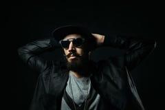 L'homme barbu dans des lunettes de soleil a étreint ses mains derrière son hea Photo stock