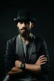 L'homme barbu dans un chapeau de lanceur a plié ses bras à travers son coffre Photographie stock