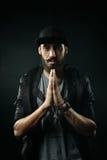 L'homme barbu dans une prière adaptée de chapeau Images stock