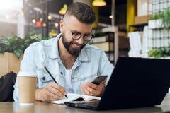 L'homme barbu de hippie s'assied à la table devant l'ordinateur portable et écrit dans le carnet, étudiant se prépare aux examens photo libre de droits