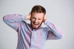 L'homme barbu fâché bel a fermé des oreilles à la main et des cris images stock