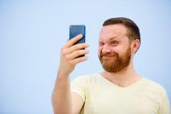 L'homme barbu gai cligne de l'oeil au téléphone, approprié à faire de la publicité, sur un fond bleu Photos libres de droits