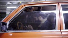 L'homme barbu mûr avec les cheveux foncés ferme la fenêtre de voiture rouge dans le garage souterrain clips vidéos