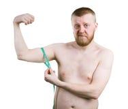 L'homme barbu mesure la taille de votre biceps photographie stock