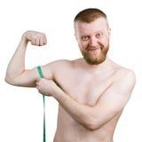 L'homme barbu mesure son petit biceps image stock