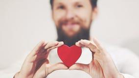 L'homme barbu remet tenir le symbole d'amour de forme de coeur Photographie stock