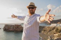 L'homme barbu roux de voyageur de hippie avec les mains ouvertes se tient avec le sien de nouveau à la mer et sourit dans les ray Image libre de droits