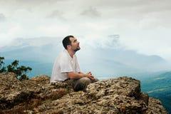 L'homme barbu s'assied sur la montagne Photographie stock libre de droits