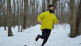 L'homme barbu sportif courant dans la forêt sur la neige a couvert le chemin le jour d'hiver banque de vidéos