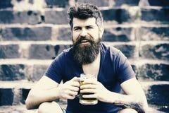 L'homme barbu tient la tasse de bière, boit de la bière extérieure Concept de bière de métier L'homme avec la longue barbe semble photos libres de droits
