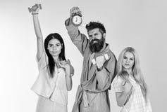 L'homme barbu tient le réveil Concept de mode de vie de forme physique L'entraîneur, macho avec les filles attirantes font des ex photographie stock