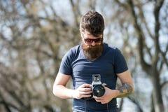L'homme barbu travaille avec l'appareil-photo de vintage Homme avec la barbe et moustache sur le visage concentré, branches sur l Photos libres de droits