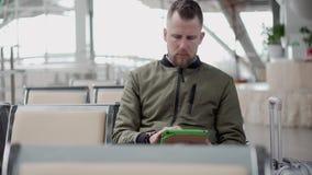 L'homme barbu utilise le comprimé avec le wifi libre dans la salle d'attente de l'aéroport banque de vidéos