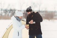 L'homme barbu versent le thé chaud à son amie Image stock