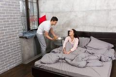 L'homme bel a apporté le petit déjeuner dans le lit tandis que son amie se réveillait Photo stock