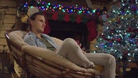 L'homme bel aux cheveux longs boit du thé dans la nuit de Noël par l'arbre décoré banque de vidéos