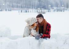 L'homme bel chuchote quelque chose drôle dans l'oreille de son amie riante Emplacement de village d'hiver Photos stock