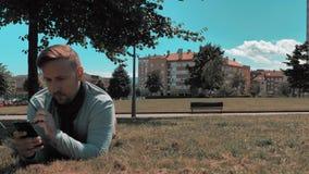 l'homme bel détendent en parc de quartier de la ville banque de vidéos