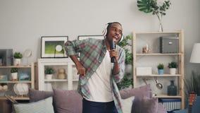 L'homme bel d'Afro-américain dans des écouteurs écoute la musique, danse et chante dans à télécommande dedans banque de vidéos