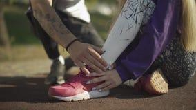 L'homme bel d'oung s'occupe de la fille qui s'est foulée sa jambe banque de vidéos