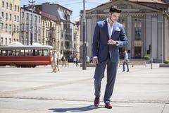 L'homme bel a d'une manière élégante habillé regarder sa montre Image stock