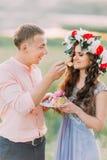 L'homme bel dans l'amie de alimentation de chemise de pêche avec le morceau de gâteau a décoré les fleurs roses Photographie stock