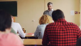 L'homme bel de haut maître d'école parle aux étudiants qui s'asseyent aux tables dans la salle de classe et le sourire Éducation