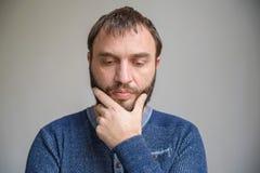 L'homme bel de portrait touche sa pensée de barbe image stock