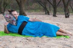 L'homme bel embarrassé de transsexuel avec composent, petit pain de cheveux se trouvant sur le sable dans le kimono bleu, tenant  image libre de droits