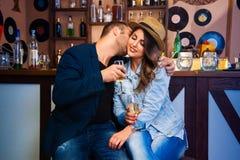 L'homme bel embrassant l'amie sur la joue et eux boivent le cham Photos stock