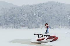 L'homme bel embrasse sa belle amie dans la joue tout en se tenant sur le pré près du bateau neigeux et Photo libre de droits