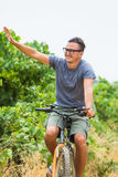 L'homme bel en verres de soleil sourit tout en faisant un cycle en parc Images libres de droits