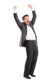 L'homme bel enthousiaste d'affaires avec des bras a augmenté dans le succès Images stock