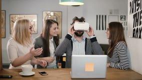 L'homme bel essaye l'APP pour des verres de réalité virtuelle de casque de VR ses amis et collègues le soutenant dans le bureau m Photo stock