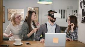 L'homme bel essaye l'APP pour des verres de réalité virtuelle de casque de VR ses amis et collègues le soutenant dans le bureau m Photographie stock libre de droits