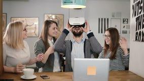 L'homme bel essaye l'APP pour des verres de réalité virtuelle de casque de VR ses amis et collègues le soutenant dans le bureau m Photographie stock