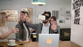 L'homme bel essaye l'APP pour des verres de réalité virtuelle de casque de VR ses amis et collègues le soutenant dans le bureau m Photos stock
