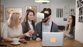 L'homme bel essaye l'APP pour des verres de réalité virtuelle de casque de VR ses amis et collègues le soutenant dans le bureau m Image libre de droits