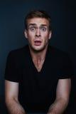 L'homme bel est effrayé de ce qu'il a vu avec la chemise noire de v-cou images stock