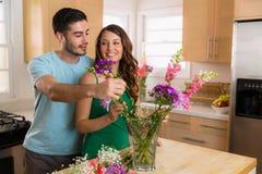 L'homme bel et la jolie femme sont dans l'amour comme nouveaux mariés dans leur nouvelle maison mettant des fleurs dans un vase Photographie stock
