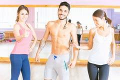 L'homme bel heureux avec des personnes de groupe dans la forme physique classent Image stock