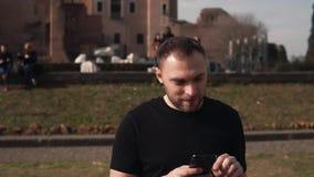 L'homme bel l'Europe de visite de touristes pour des vacances, se sent heureux, prend les photos de la ville, vues sur le smartph banque de vidéos