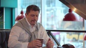 L'homme bel mûr dans une chemise blanche avec le chandail boit du café nouvellement fabriqué de matin clips vidéos