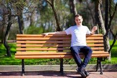 L'homme bel marchant en parc et s'assied sur le banc et l'amie de attente Photos stock