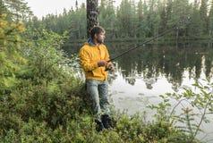 L'homme bel pêche sur le rivage du beau lac de forêt Images libres de droits